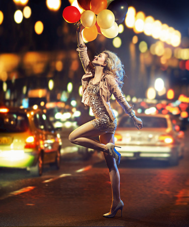 vestido de noche: Amante de la diversión señora que sostiene un manojo de globos