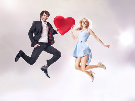 Fine photo of cheerful couple holding a cartoon heart Standard-Bild