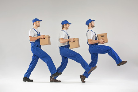 Three builders walking with boxes photo