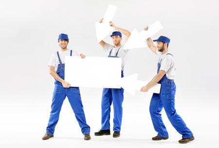 Three cheerful workers with empty board 版權商用圖片