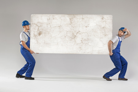 クラッシュしたボードを運ぶ 2 つの労働者