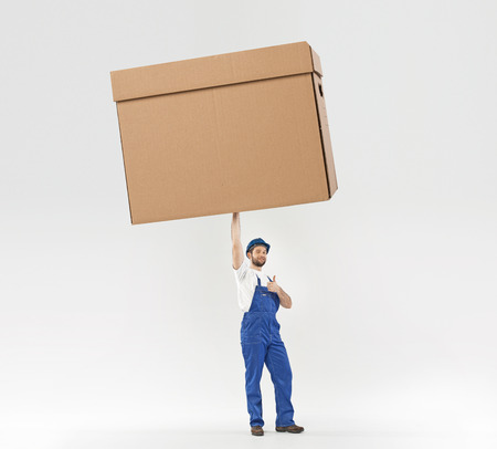 Little builder holding a huge paper box photo