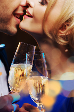 lovely couple: Cheerful couple kissing and drinking a champagne