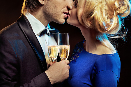 glases: Kissing young couple holding glases of a champagne Stock Photo