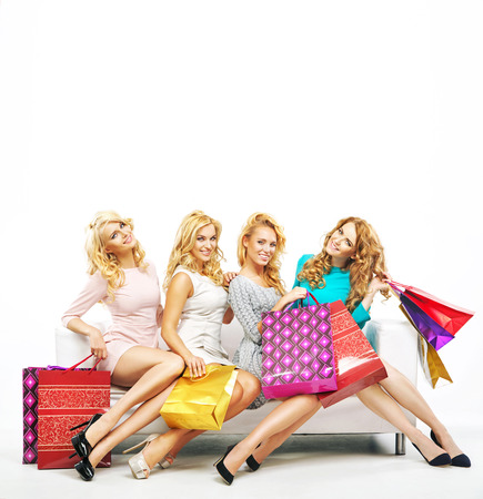Four cheerful girlfriends with a lot of shoppings photo
