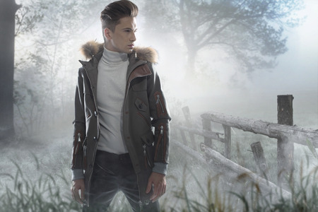 Young handsome man on the  frozen county meadow photo