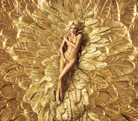 Blond lady lying on the golden wings Stock Photo