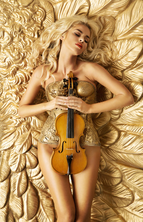 sexy women naked: Conceptual photo of golden woman holding a violin Stock Photo