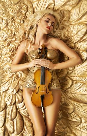 sexy nackte frau: Konzeptionelle Foto der goldenen Frau, die eine Violine