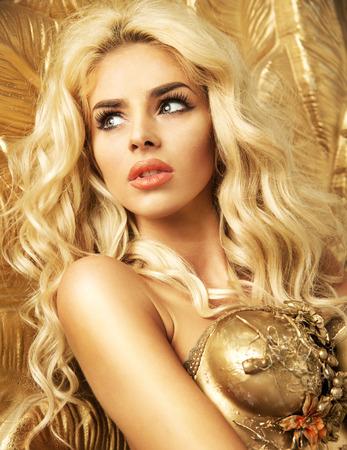 mujeres jovenes desnudas: Señora rubia atractiva entre el oro Foto de archivo