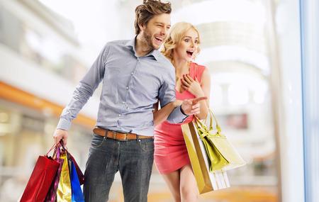 笑いながら若いカップルは店のウインドーを見つめて