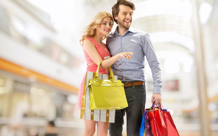 shopping malls: Young cheerful couple with a bunch of shopping bags