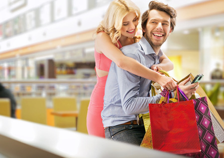 woman buying: Young cheerful marriage couple in the shopping mall