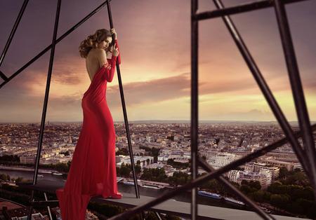 vestido de noche: Elegante mujer de pie en el borde de la azotea