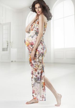 Brunette pregnant lady wearing flowered dress photo