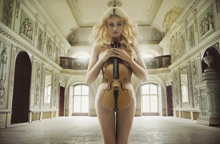 Sensual female musician holding the old violin