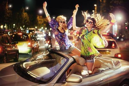 Due donne allegre che ballano in cabriolet