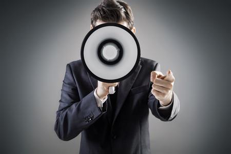 Elegant manager holding a huge megaphone Standard-Bild