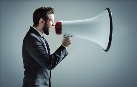 mládí: Konceptuální fotografie manažera křičí přes megafon Reklamní fotografie