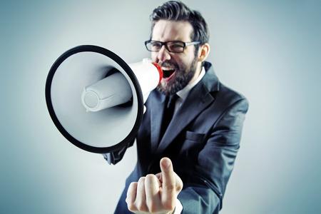megafono: Joven empresario agresivo gritando sobre el meg�fono Foto de archivo