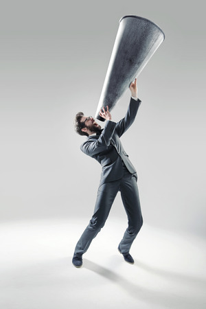 Elegante manager schreeuwen over de enorme megafoon