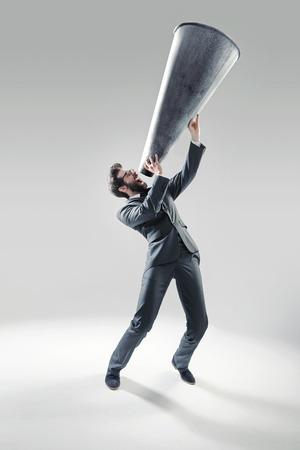 megafono: Gerente elegante gritando sobre el enorme megáfono Foto de archivo