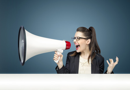 Young pretty businesswoman yelling over megaphone