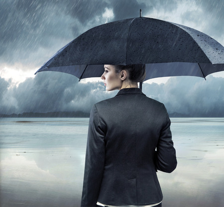 pessimist: Businesswoman standing with an black umbrella Stock Photo