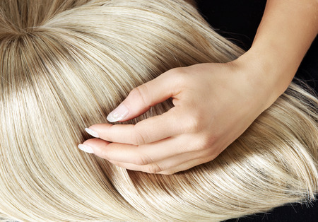 blond streaks: Straight blond wig combing by a woman