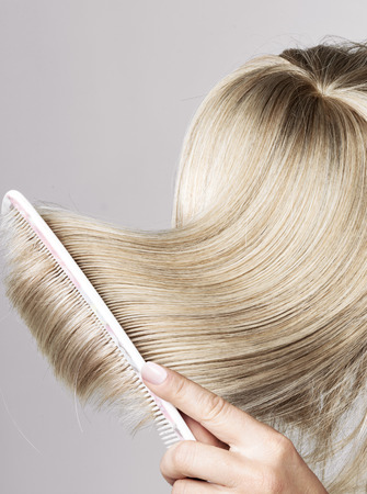 blond streaks: Blond fresh hairpiece brushed by a woman