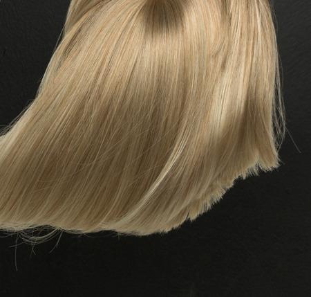 Dense, straight blond wig lying on dark background