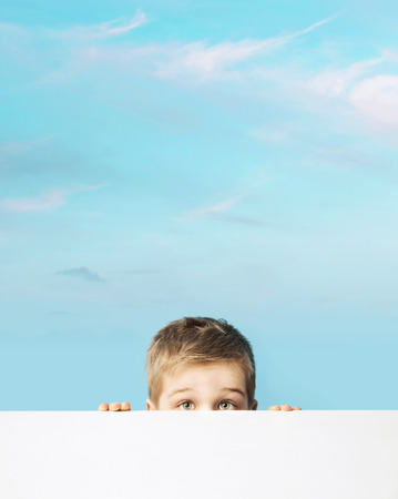 full face: Fine portrait of a small boy hiding behind an empty board