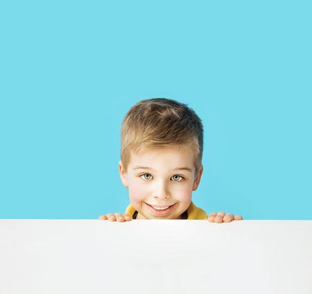 Klein und niedlich lächelnde Junge, der Gesichter
