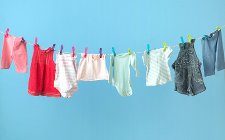 Colorful babys clothing getting dry Imagens