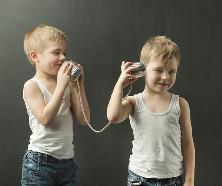 toy phone: Cute little siblings talking on the toy phone Stock Photo