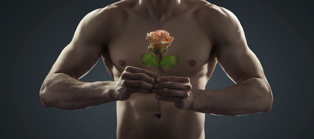 strongman: Handsome strongman holding a flower Stock Photo