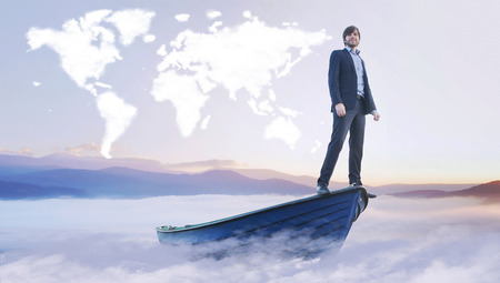 Young businessman under the cloud world map photo