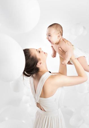 彼女の最愛の幼児を保持しているかなりのママ 写真素材