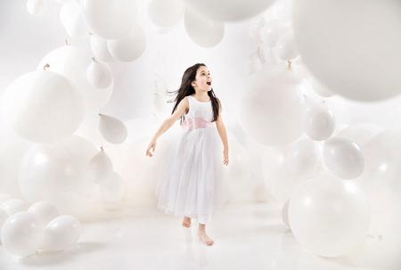 多数の風船の中で喜んでいる子供 写真素材