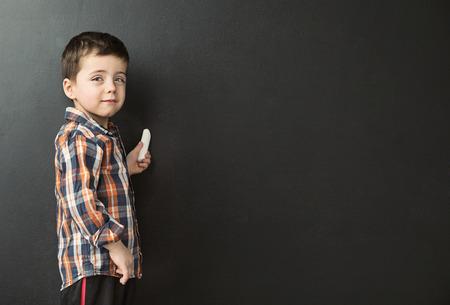 ditch: Cute little boy drawing on the blackboard