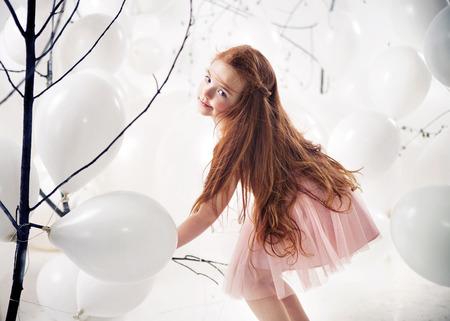 ginger flower plant: Cute little girl playing white balloons Stock Photo