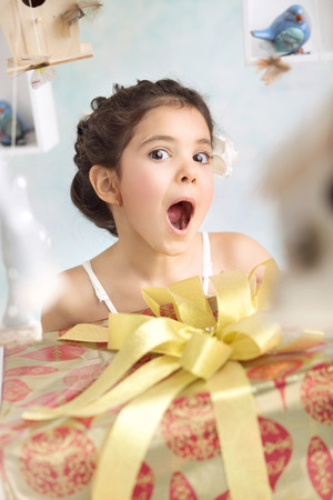 little girl surprised: Pretty surprised girl with birthday presents