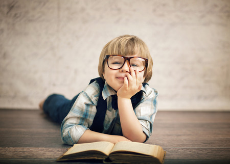 kid reading: Clever boy reading a book