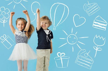 small articles: Two cute children over the drawings background Stock Photo