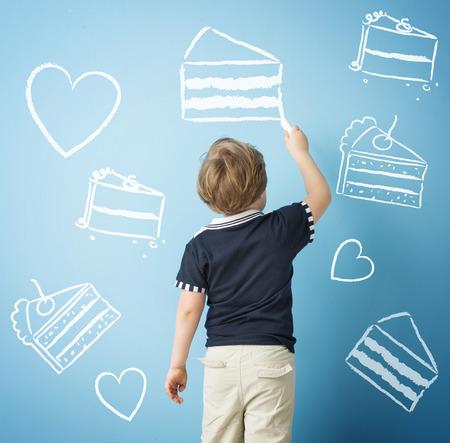 チョークでお菓子を描く幸せな子