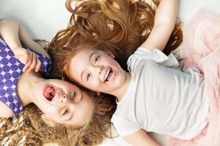 Zwei fröhliche Kinder, die zusammen lachen