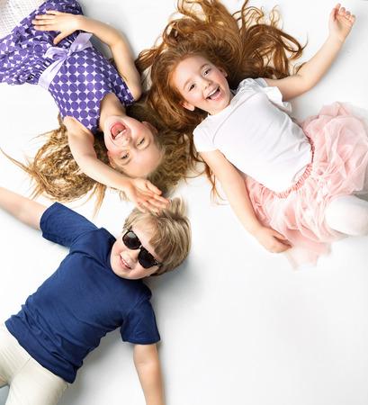 Портрет маленьких братьев и сестер, лежащих на белом фоне