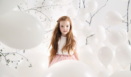numerous: Cute girl among numerous white balloons