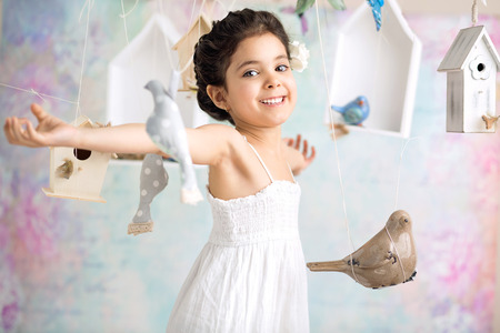 cheerful girl among wooden birds photo