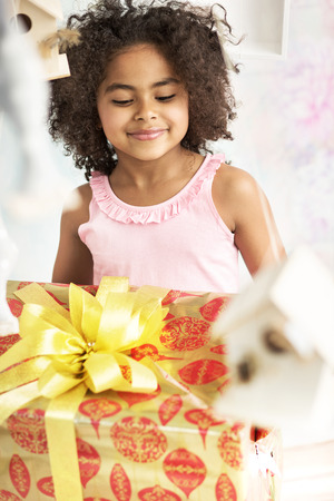 cadeau anniversaire: Mignon petite fille regardant le cadeau d'anniversaire